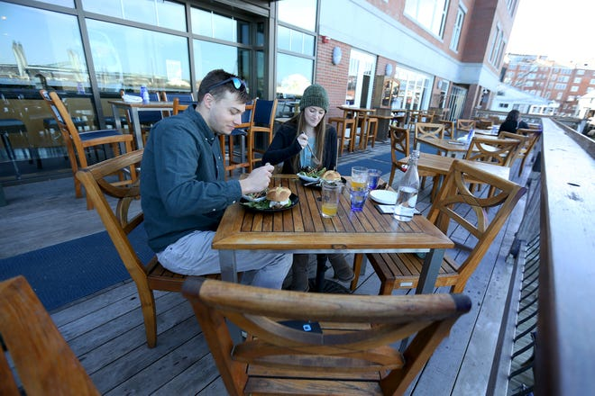 From left, Kittery residents Griffin Damon and Alyssa Moreau enjoy lunch on the outdoor deck of Surf on Tuesday afternoon in Portsmouth.