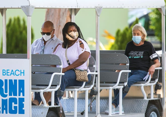 People are brought by tram from the parking lot to the Wells Recreation Center in Riviera Beach for their Covid-19 vaccinations Thursday, March 18, 2021.