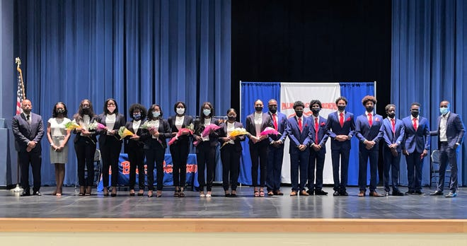 Graduates of the 2021 Suits for Seniors program pose with supporters during the ceremony at Palm Beach Gardens High School on March 10.