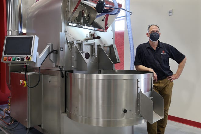 Rik Kleinfeldt is moving his New Harvest Coffee Roasters to the Farm Fresh Food Hub on Sims Street in Providence. He poses next to his state-of-the-art coffee roaster.