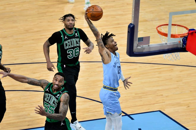 Memphis Grizzlies guard Ja Morant goes up for a dunk against Boston Celtics guard Jeff Teague in the second half of an NBA basketball game Monday in Memphis, Tenn.