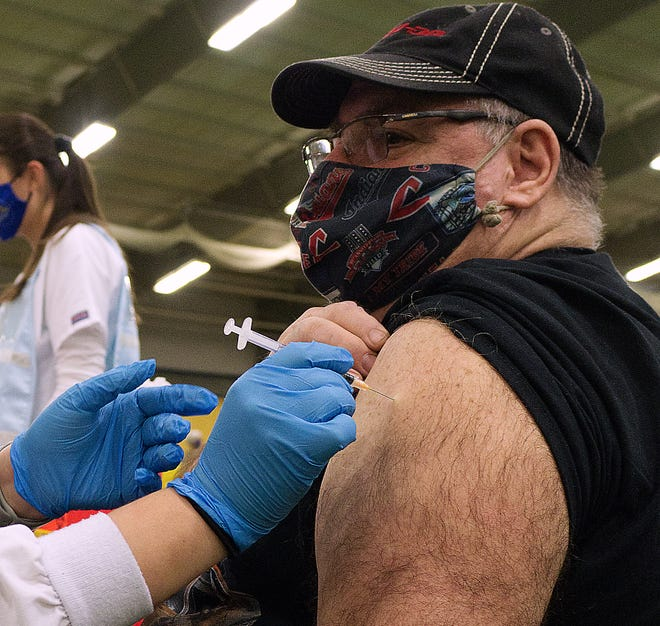 Mark Finney of Ravenna gets his first dose of the Moderna vaccine from Kent State University nursing student Sara Van Gelder at the Portage County Health District vaccine clinic on March 23.