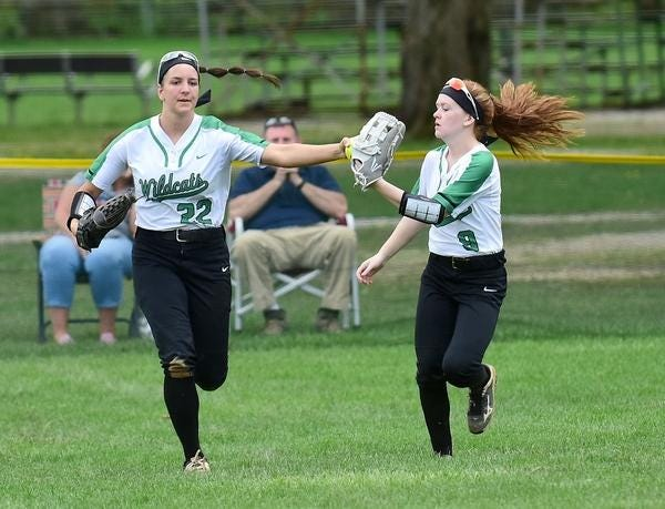 Paige Halliwill, left and now playing for Marshall University, and Olivia Mason, one of two returning outfielders for Mogadore, bump gloves on the way back to the dugout last season.