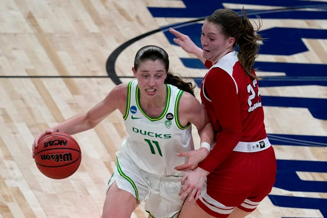 Former Oregon guard Taylor Mikesell (11) drives past South Dakota guard Chloe Lamb (22) during the first half of an NCAA Tournament game last month. (AP Photo/Charlie Riedel)