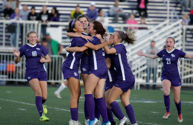 Devyn Simmons (left), Sahve Beller and Tessa Bretschneider meet in the middle as teammates swarm in to celebrate a goal during a game in 2019.