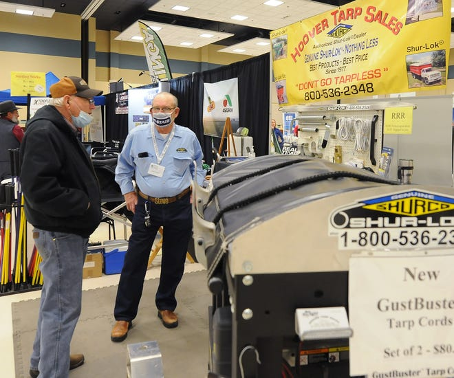 Larry Dahlsten, of rural Lindsborg, visits with Steve Hoover, co-owner of Hover Tarp Sales of Abilene, at the booth inside of the Great Plains Manufacturing Convention Hall, former Heritage Hall, during the 56th annual Mid-America Farm Exposition on Tuesday.