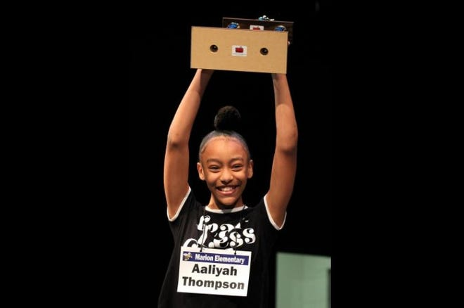 Aaliyah Thompson hoists her trophy after winning the 2020 Star Spelling Bee.