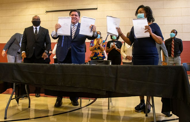 """Illinois Governor JB Pritzker, center, is joined by Illinois State Rep. Sonya Harper, D-Chicago, right, and members of the Illinois Black Legislative Caucus, in holding up the signed bills that make up the caucus' economic development """"pillar"""" at Union Baptist Church in Springfield, Ill., Tuesday, March 23, 2021. [Justin L. Fowler/The State Journal-Register]"""