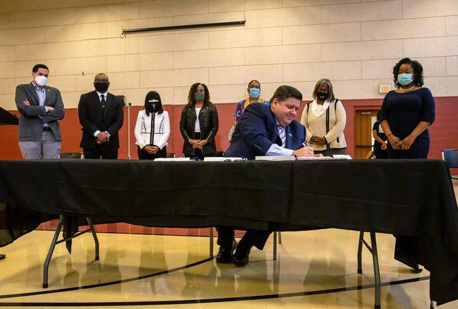"Gov. JB Pritzker signs four bills that make up the Illinois Black Legislative Caucus' economic development ""pillar"" at Union Baptist Church in Springfield on Tuesday, March 23, 2021. [Justin L. Fowler/The State Journal-Register]"