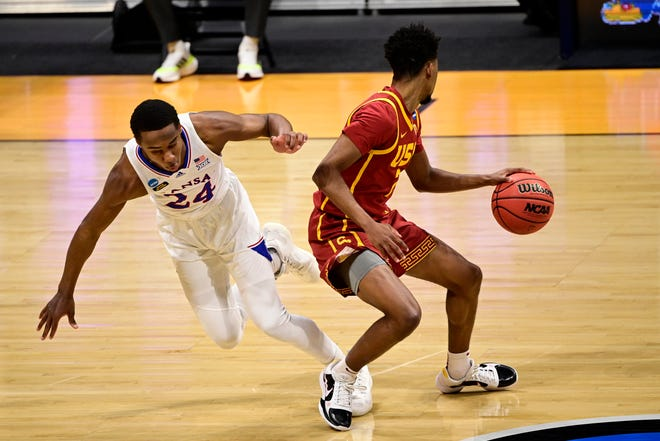 Kansas basketball's Bryce Thompson, left, stumbles while trying to guard USC's Tahj Eaddy during the first half of Monday's game at Hinkle Fieldhouse in Indianapolis. The Trojans held a 19-point lead at half time en route to their comfortable 85-51 victory in the second-round matchup at the NCAA Tournament.