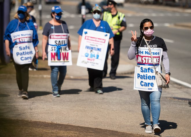 RN Yarelis Diaz flashes a peace sign while walking the picket line with St. Vincent Hospital nurses Tuesday.