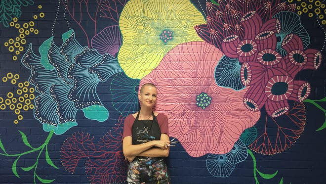 Heather Clements poses with her mural that graces the children's art studio in the Panama City Center for the Arts. She started work on her portion of a shared mural at Sixth Street and Harrison Avenue this week.