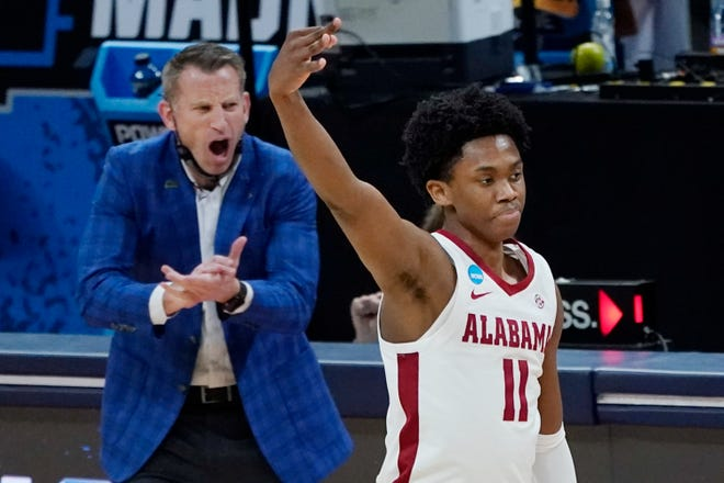 Alabama's Joshua Primo (11) celebrates after scoring against Maryland as Alabama head coach Nate Oats applauds him during the first half of a college basketball game in the second round of the NCAA tournament at Bankers Life Fieldhouse in Indianapolis Monday, March 22, 2021. (AP Photo/Mark Humphrey)
