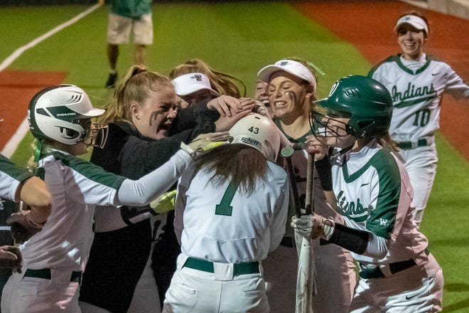 Waxahachie softball players celebrate a two-run homer by Kennedi Massey (7) at the plate during Friday night's District 11-6A game against Duncanville. Massey finished the night with five RBI as the Lady Indians won, 10-7.