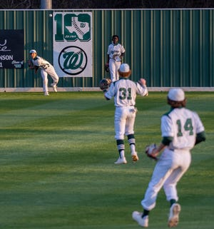 Waxahachie junior leftfielder Jacob Cruz (25) throws the ball in as centerfielder Xavien Thompson and infielders Lucas Ferguson (31) and Casey Kelly (14) look on during Friday night's District 11-6A game against Duncanville at Richards Park.
