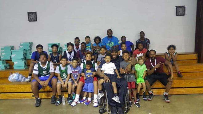 The Boys and Girls Club kids gather around for a picture with Tim Alexander.