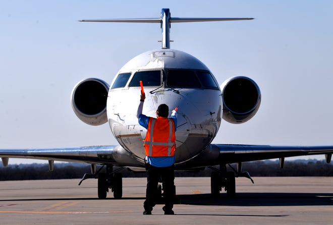 Josh Drury signals a confirmation to the pilot of a United Express SkyWest flight at Abilene Regional Airport March 19, 2021. The carrier, which offers direct air service to Houston from Abilene, began operations in the Abilene Oct. 21. It announced Tuesday it was leaving in October of this year.