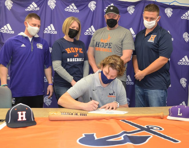 Lakeview's Mason Belmore is joined by family and coaches as he signs a commitment paper to play baseball at Division III Hope College.