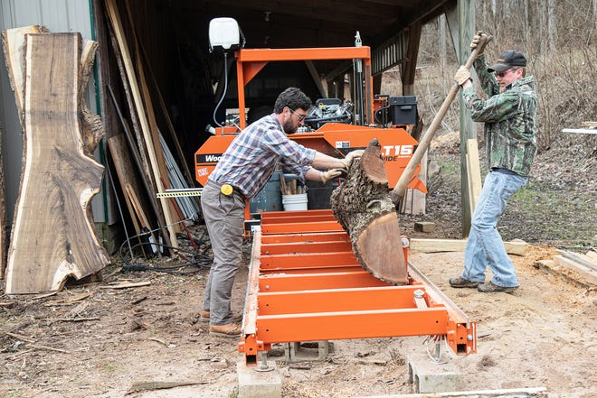 Jamie Lambert, left, and his soon-to-be father-in-law Brian Glandon flip a log to start cutting the other side at his home in Frankfort, Ohio. Lambert makes custom furniture from reclaimed wood.