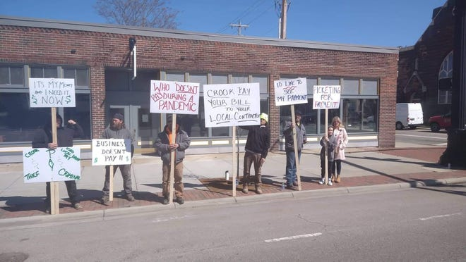 Protestors gather in front of Vision Source over payment dispute.