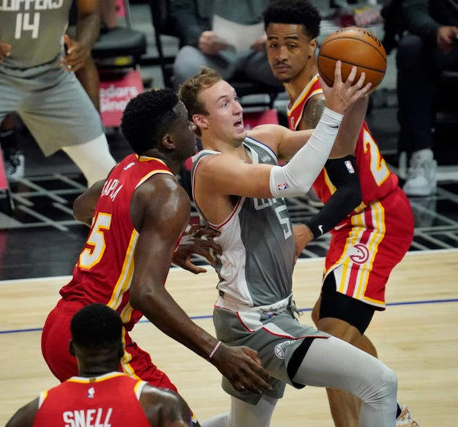 Clippers guard Luke Kennard (5) moves to the basket past Atlanta Hawks center Clint Capela (15) and forward John Collins (20) during the third quarter at Staples Center on March 22.