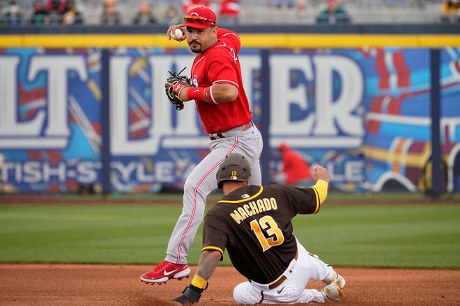 Cincinnati Reds shortstop Eugenio Suarez forces out San Diego Padres' Manny Machado (13) at second base on a ball hit by Eric Hosmer during the first inning of a spring training baseball game on March 23 in Peoria, Arizona.