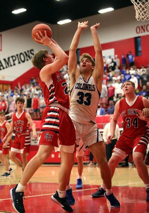 St. Henry forward Jude Bessler (22) scores over Cov Cath center Mitchell Rylee in the game between Covington Catholic and St. Henry high schools at Holmes High School March 22, 2021.