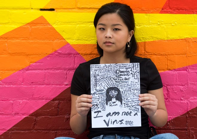 "Lily Hubbard of Henderson, Ky., poses with a drawing she made toward the beginning of the COVID-19 Pandemic Monday, March 22, 2021. The 18-year-old high school senior, who was adopted from China as a baby, said she was feeling very frustrated and overwhelmed and turned to art as a release.  ""Ultimately when I thought about COVID and America's opinion of China I was thinking I know racism but I can't imagine how bad it could possibly be. Now jumping a year later it's pretty horrible."""