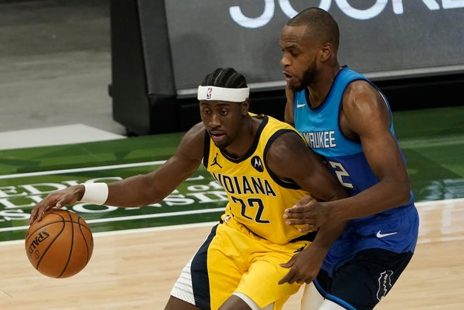 Indiana Pacers' Caris LeVert battles Milwaukee Bucks' Khris Middleton during the first half Monday, March 22, 2021, in Milwaukee. (AP Photo/Morry Gash)