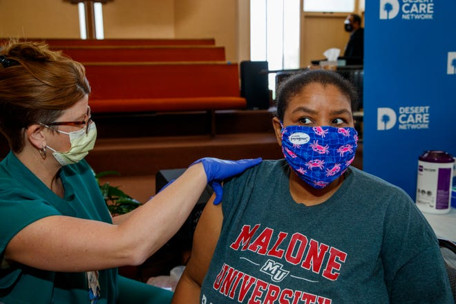 Felicia Wash, 49, of Palm Springs receives the Pfizer COVID-19 vaccine from Desert Care Network registered nurse Sherry Elliott at Ajalon Baptist Church in Palm Springs, Calif., on March 23, 2021. Wash, a member of the church, also volunteered at the vaccine clinic.