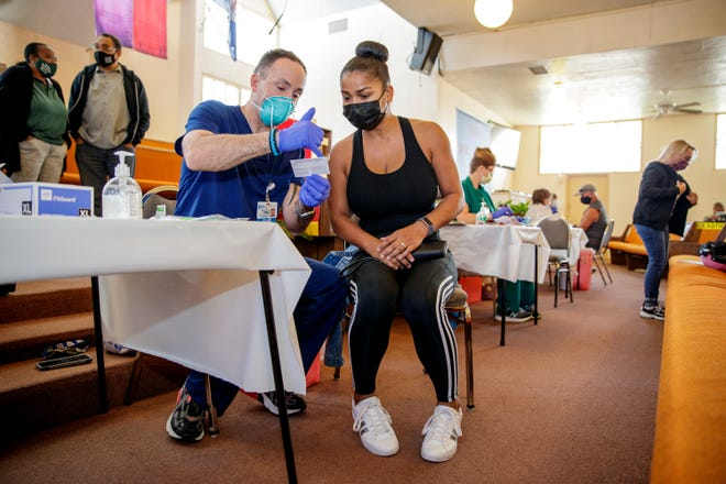 Desert Care Network registered nurse Brian Walker shows Ashley Villarreal, 33, of La Quinta her vaccination card after receiving the Pfizer COVID-19 vaccine at Ajalon Baptist Church in Palm Springs, Calif., on March 23, 2021.