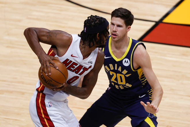 Indiana Pacers forward Doug McDermott (20) guards Miami Heat forward Trevor Ariza (0) during the second half of an NBA basketball game, Sunday, March. 21, 2021, in Miami. (AP Photo/Joel Auerbach).