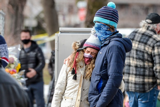 Esther Baumann, left, hugs Fabrizio Giorgetta at a memorial outside a King Soopers grocery store where multiple people were killed during a shooting on March 23, 2021.