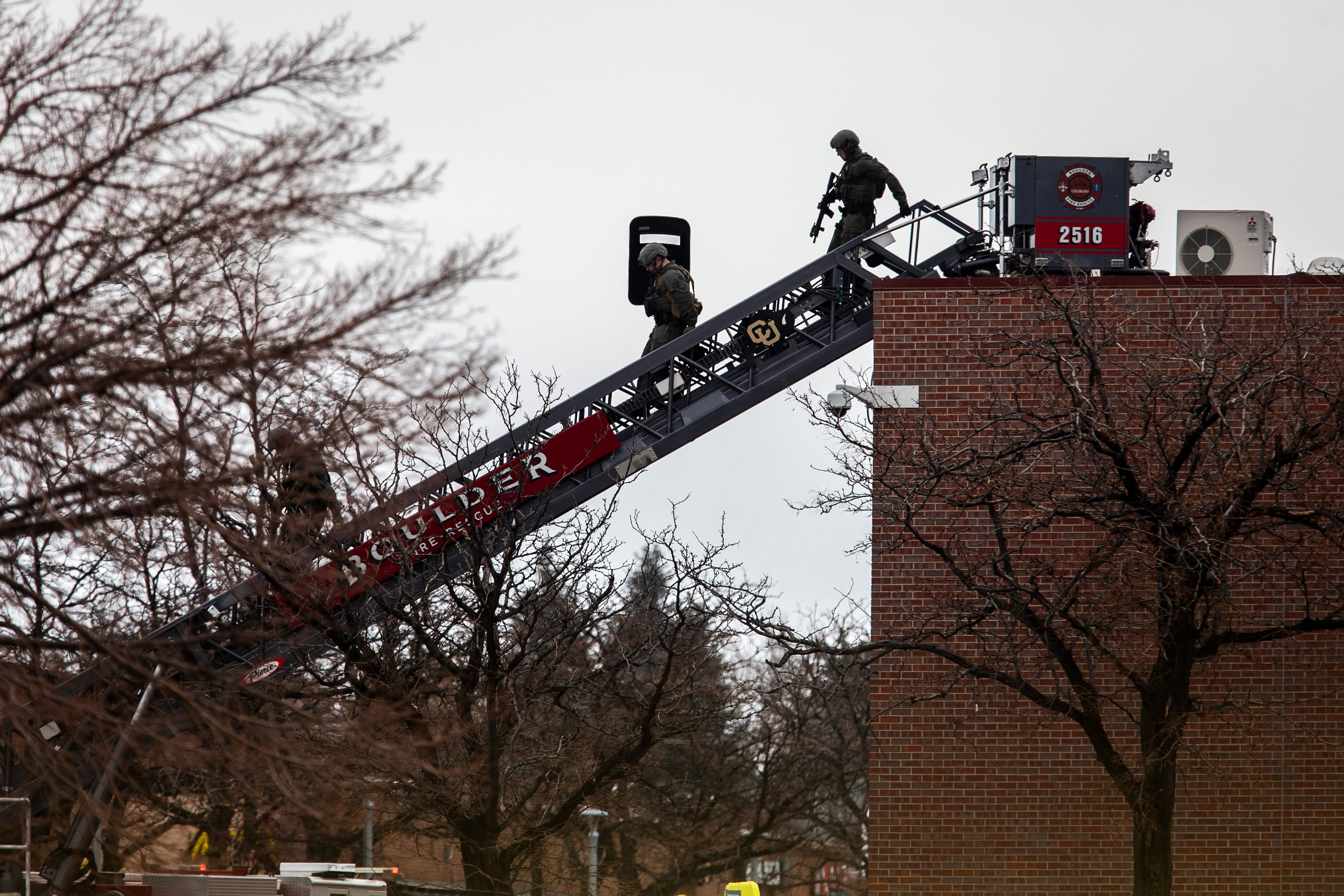 SWAT teams descend from the roof on a fire ladder after a gunman opened fire at a King Sooper's grocery store on March 22, 2021 in Boulder, Colo. Ten people, including a police officer, were killed in the attack.