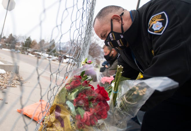 King Soopers security guard Norman Suazo adds flowers to a memorial outside the company's store after a mass shooting where 10 people died at King Soopers in Boulder, Colo. on Tuesday, March 23, 2021.