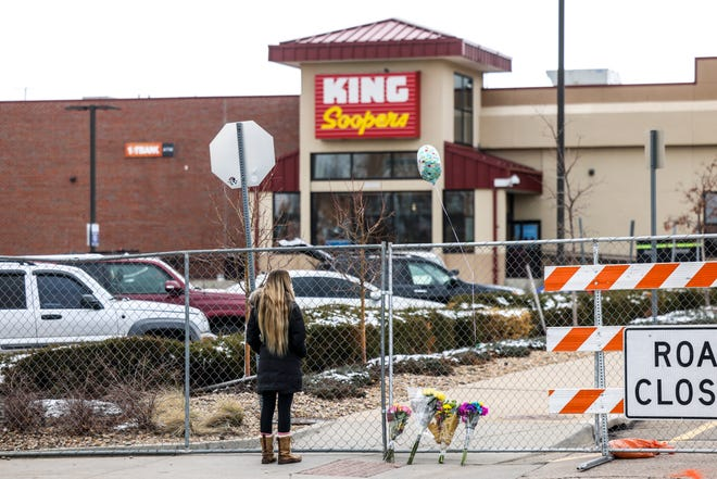 A woman watches as police officers continue their investigation of a mass shooting at a supermarket on March 23, 2021, in Boulder, Colorado.