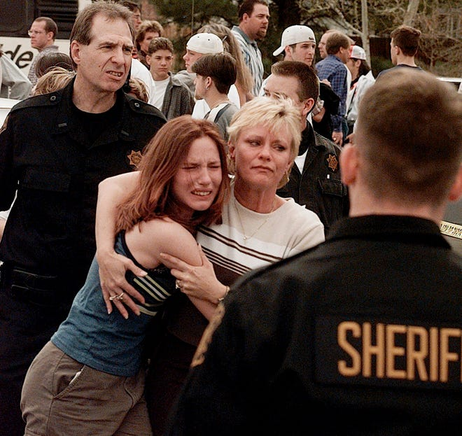 In this April, 20, 1999, file photo, a woman is pictured embracing her daughter after they were reunited following a shooting at Columbine High School in Littleton, Colorado. The shooting shocked the country as it played out on TV news shows from coast to coast after two students killed 12 others and a teacher before dying by suicide.