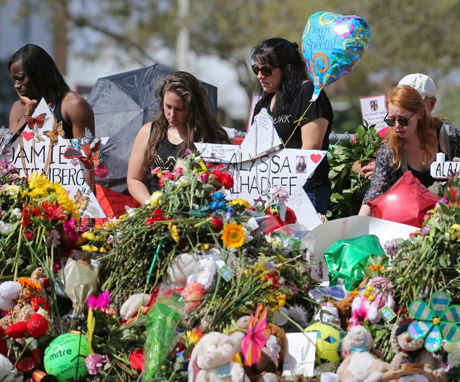 Mourners bring flowers to a memorial for  victims of a shooting at Marjory Stoneman Douglas High School in Parkland, Fla. Seventeen students and staff were killed in 2018 in the mass shooting on Valentine's Day.