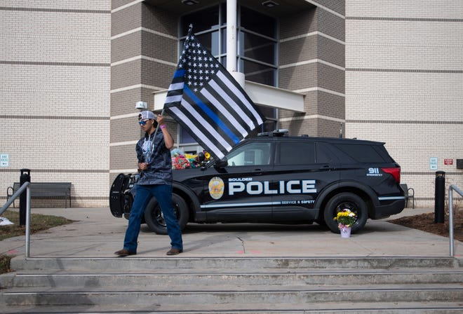 JJ Cone carries a Blue Lives Matters flag after placing flowers on a patrol car outside the Boulder Police Department after a mass shooting where 10 people died, including Boulder police officer Eric Talley, in Boulder, Colo. on Tuesday, March 23, 2021.