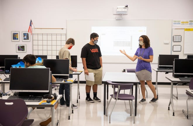 Christina Strnad, right, is shown last fall teaching a graphic design class at Thrall High School.