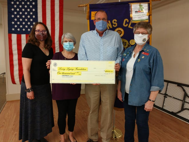 While Library Director Melissa Mallinak (left) looks on, Loudonville Lions Club President Janet Abee (second from left) and Perrysville Lions President Carolyn Beck (right) present an oversized check to Jamie Black, president of the Living Legacy Foundation of the Loudonville Public Library, money raised by the two clubs for the 24-hour library in Perrysville. Presentation was made at the Loudonville Lions meeting Tuesday, March 23.