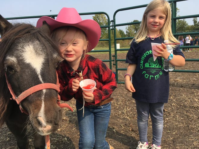 Corrie Perkinsgives some love to Cricket the mini-pony asRuby Handsakerlooks on during a ranch program at Cultivating Hope Farms last fall. Cricket was adopted from the Des Moines Animal Rescue League and is one of several rescued critters that are animal helpers at the farm.