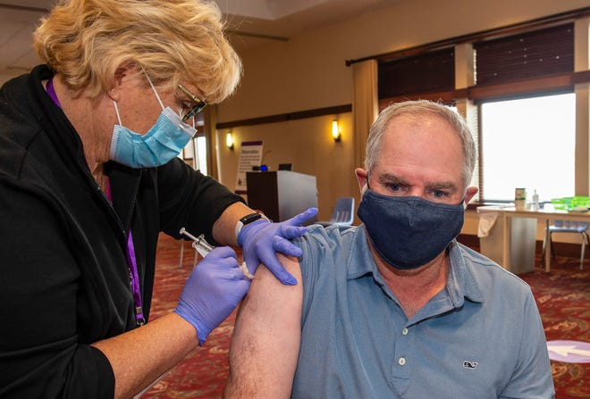 Retired nurse Kathy Harrison, of Butler, gives Brian Kaufmann of Cranberry Township his first COVID-19 Pfizer vaccine during a clinic at Cumberland Woods Conference Center in McCandless Township.