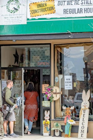 A window washer working on East Main Street, Barnesville, performs a random act of kindness, opening the door for a store patron at Bless Your Heart Folk Art.
