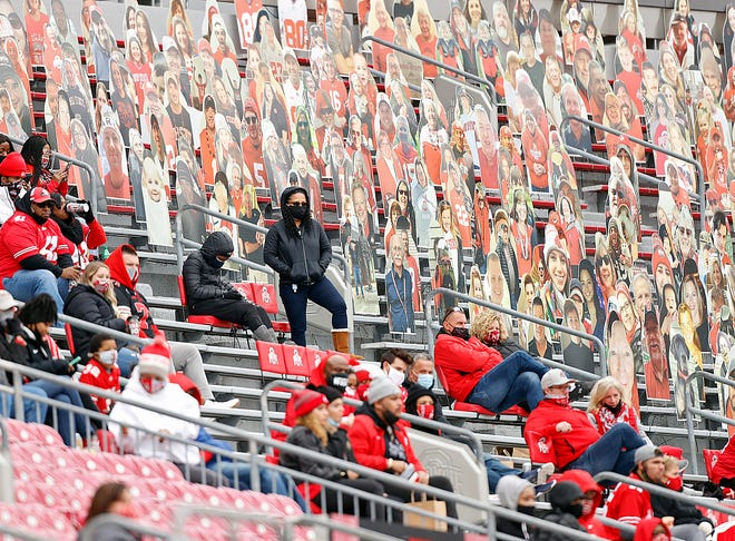 Ohio State family members watch from the stands next to cardboard cutouts of fans during a football game against Nebraska on Oct. 24 at Ohio Stadium.
