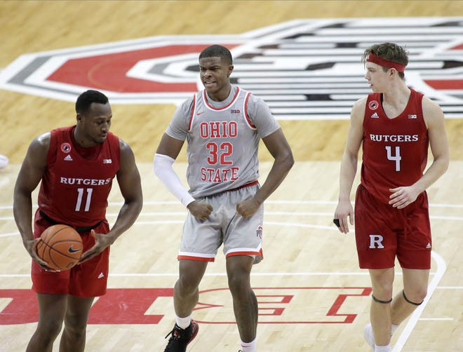 Ohio State Buckeyes forward E.J. Liddell (32) reacts after making a shot while defended by Rutgers Scarlet Knights forward Mamadou Doucoure (11) during the second half of Wednesday's NCAA Division I basketball game at Value City Arena in Columbus, Oh. on December 23, 2020.