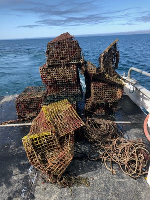 "Recovered derelict traps, also known as ""ghost"" traps, on the deck of the fishing vessel Adventure."