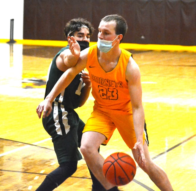 Pellston senior guard Ian Reimann (right) drives by a Beaver Island player during the first half of a Division 4 boys basketball district semifinal in Pellston on Tuesday.