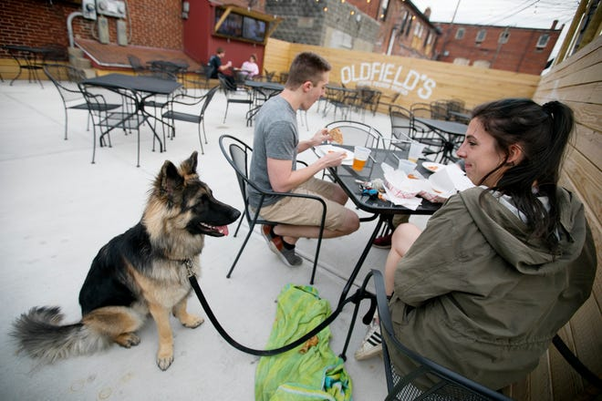 Molly Radigan, with her dog Madden, Josh Rivera and Craig Yantko, not pictured, share beer and pizza on the expanded patio at Oldfield's North Fourth Tavern on Tuesday.