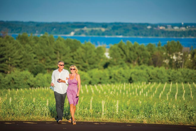 A couple walks in Hawthorne Vineyards on Old Mission Peninsula.